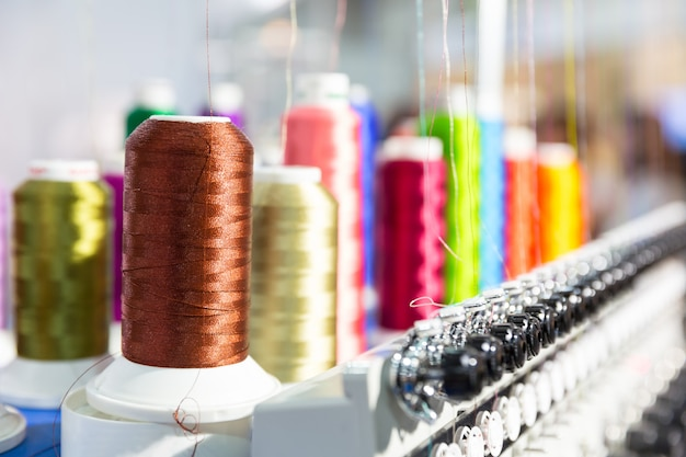 Bobine di nuovi fili closeup, macchina da cucire. fabbrica di tessuti, tessitura, produzione tessile, industria dell'abbigliamento