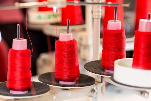 Bobine di fili rossi sulla macchina da cucire. tessuto di stoffa, tessitura, produzione tessile, industria dell'abbigliamento