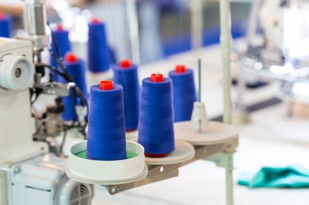 Bobine di fili sulla macchina da cucire, primo piano. fabbrica di tessuti, tessitura, produzione tessile, industria dell'abbigliamento