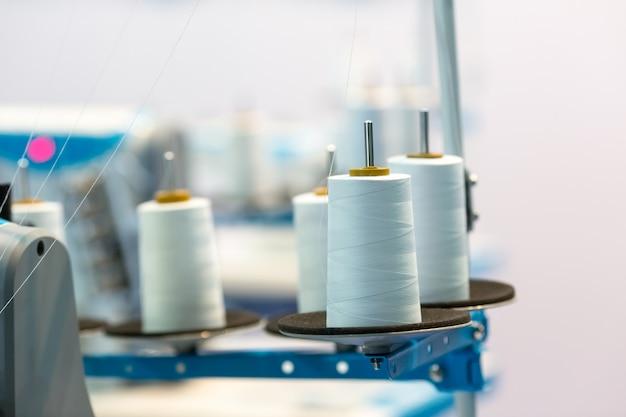 Bobine di fili bianchi sulla macchina da cucire, primo piano