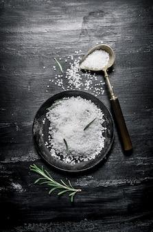 Cucchiaio e piatto nero con sale sulla superficie scura in legno