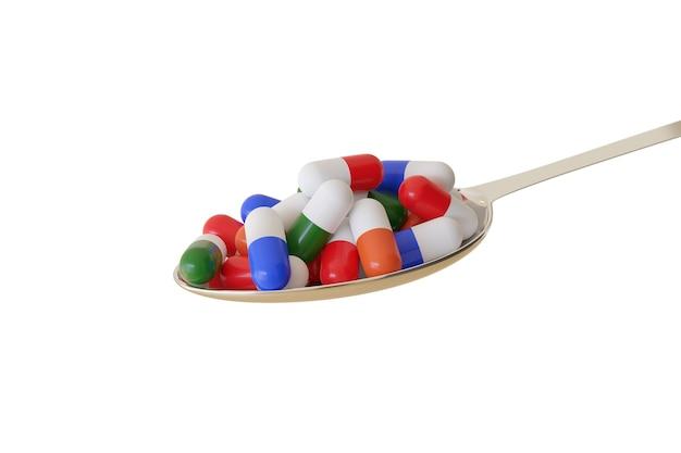 Cucchiaio pieno di diverse pillole colorate isolate su una superficie bianca.