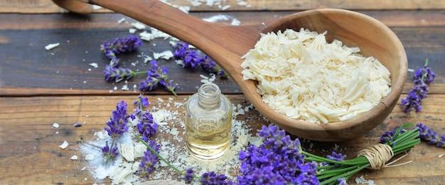 Cucchiaio pieno di scaglie di sapone con olio essenziale e fiori di lavanda sulla tavola di legno