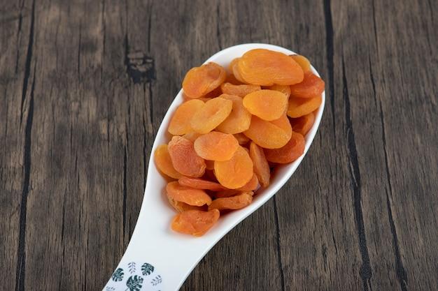 Un cucchiaio pieno di frutta albicocca secca sana su un tavolo di legno.