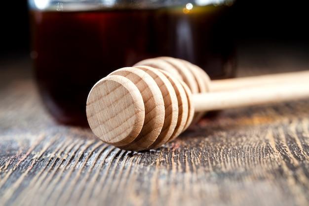 Un cucchiaio per il miele insieme al miele d'api di alta qualità, un vecchio tavolo su cui c'è un miele d'api sano e dolce e un cucchiaio di legno fatto in casa che permette di trasferire e versare il miele