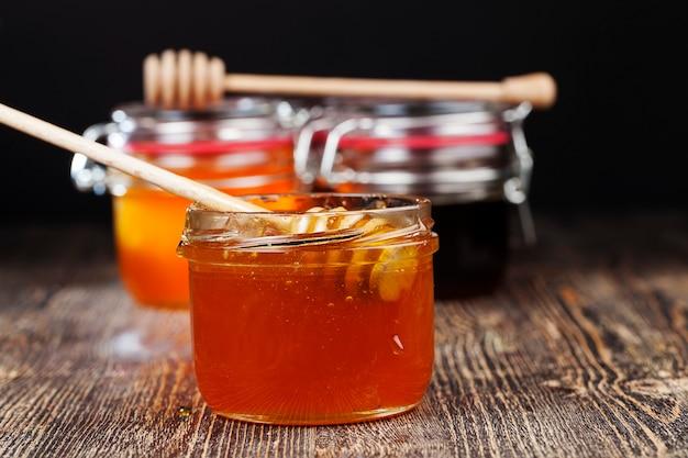 Un cucchiaio per il miele insieme al miele d'api di alta qualità