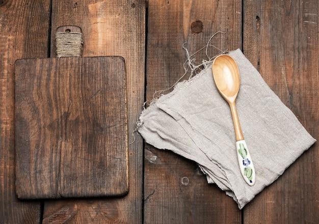 Cucchiaio e vecchio tagliere da cucina in legno rettangolare marrone e tovagliolo di lino grigio sul tavolo, vista dall'alto