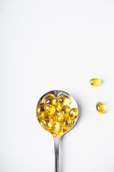 Cucchiaio di vitamine omega-3 su sfondo chiaro