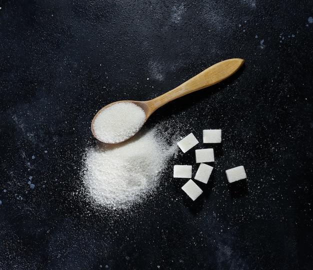 Cucchiaio di zucchero e zollette di zucchero raffinato su sfondo scuro