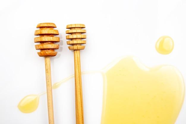 Cucchiaio con miele fresco versato su uno sfondo bianco. cibo vitaminico biologico