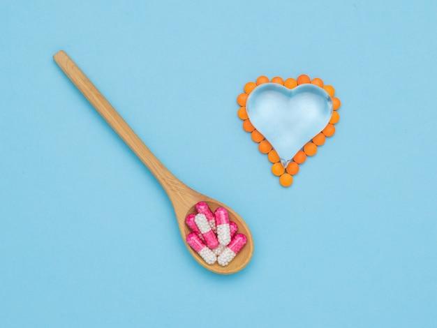 Un cucchiaio con capsule medicinali e un cuore di vetro con pillole su una superficie blu