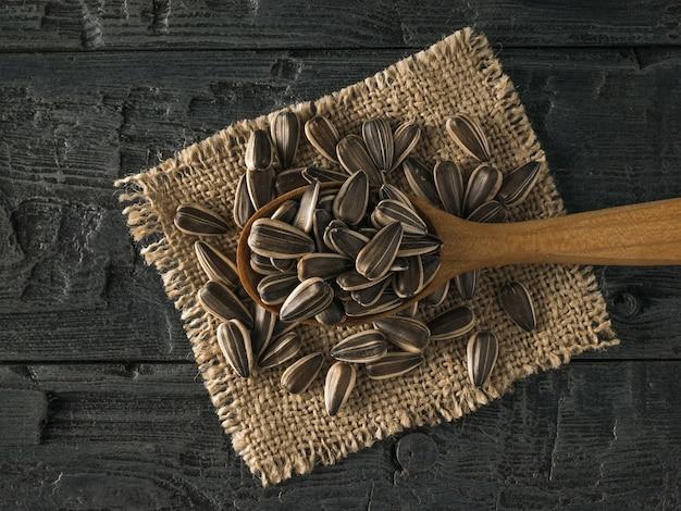 Cucchiaio con semi di girasole su un pezzo di tela su un tavolo di legno