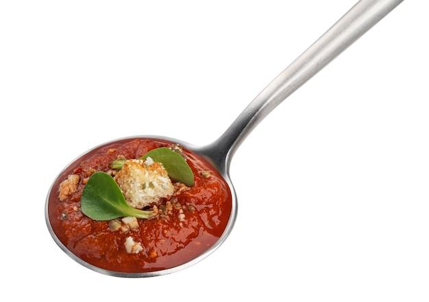Cucchiaio con zuppa di pomodoro isolato su sfondo bianco