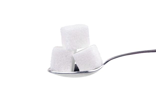 Cucchiaio con zucchero bianco su sfondo bianco