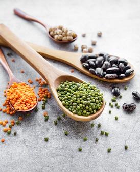 Cucchiai con diversi tipi di legumi su una superficie di cemento grigio