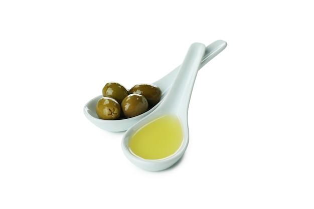 Cucchiai con olio d'oliva e olive isolati su superficie bianca
