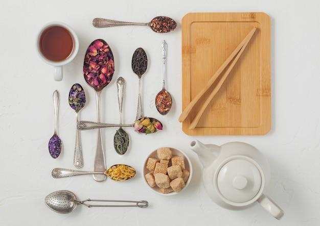 Cucchiai con vari classici e tisane su sfondo bianco con teiera e tazza, tavola di legno e infusore colino vintage. vista dall'alto