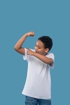 Sport, successo. ragazzo ottimista dalla pelle scura con una maglietta bianca che si tocca la mano gioendo per i muscoli forti in piedi su sfondo blu