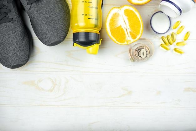 Sfondo di sport con scarpe da ginnastica, bottiglia d'acqua, frutta, nastro di misurazione e vitamine in una scatola di pillole