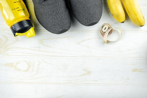 Sfondo sportivo con scarpe da ginnastica, bottiglia d'acqua, frutta e nastro di misurazione