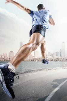 Sfondi sportivi. velocista a partire dalla pista di atletica. collage. concetto di pubblicità. l'atleta maschio che corre contro il paesaggio degli stati uniti d'america