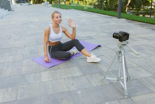 Blog sportivo. attraente giovane donna sportiva saluta i suoi seguaci all'aperto, registra sulla fotocamera su treppiede. lezione per il suo vlog di fitness