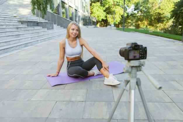 Blog sportivo. attraente giovane donna sportiva parla con i suoi seguaci dei benefici dell'esercizio all'aperto, registra sulla fotocamera su treppiede. lezione per il suo vlog di fitness