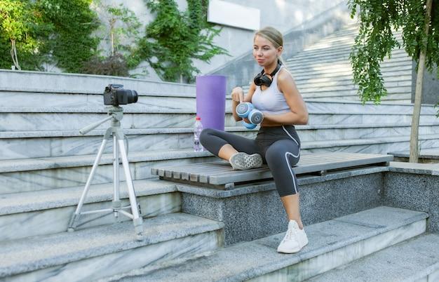 Blog sportivo. attraente giovane donna sportiva che si allena con manubri all'aperto, dimostrando esercizi per il suo blog, registra sulla fotocamera su treppiede. lezione per il suo vlog di fitness