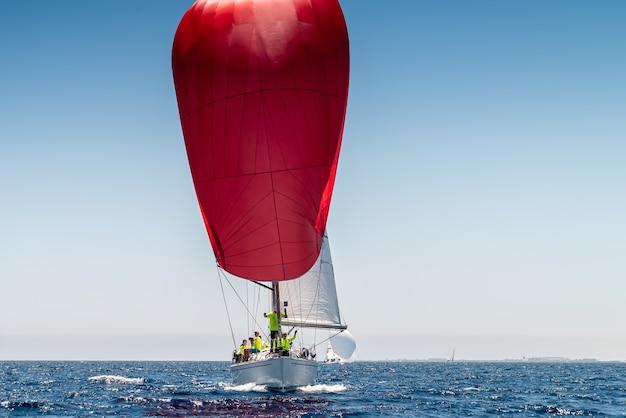 Barca sportiva con vela rossa, vista frontale