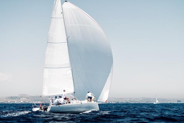 Barca sportiva con una vela bianca su regata, vista posteriore