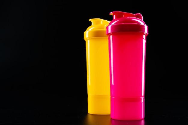 Bottiglie di sport per drink sulla superficie nera