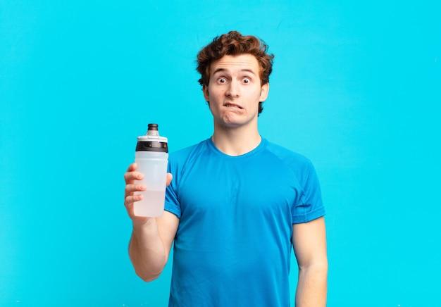 Ragazzo sportivo che sembra perplesso e confuso, mordendosi il labbro con un gesto nervoso, non conoscendo la risposta al problema. concetto di bevanda energetica