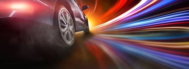 Ruota dell'auto sportiva alla deriva e fumo su sfondo colorato di illuminazione