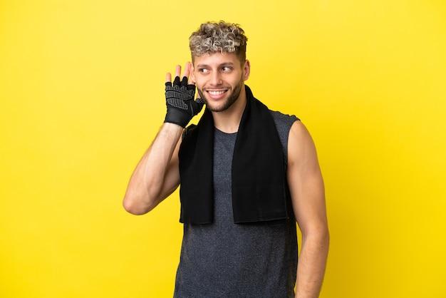 Sport uomo caucasico isolato su sfondo giallo ascoltando qualcosa mettendo la mano sull'orecchio