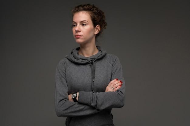 Metta in mostra la donna caucasica, immagine isolata su fondo grigio