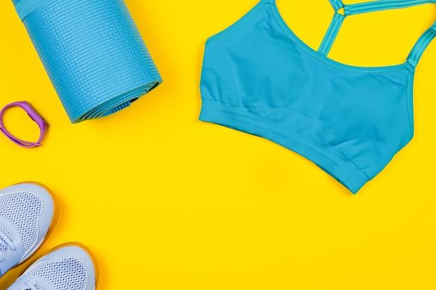 Abbigliamento sportivo e accessori su sfondo giallo.