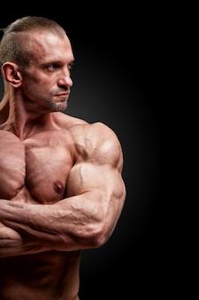 Concetto di sport. l'atleta di forma fisica con i muscoli perfetti posa sulla macchina fotografica sopra lo spazio nero.