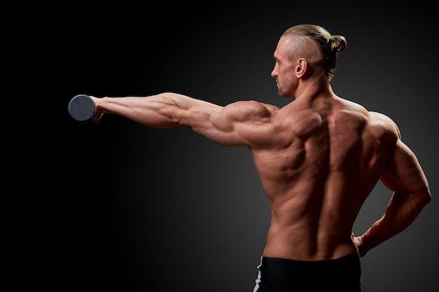 Concetto di sport. l'atleta di forma fisica con i muscoli perfetti posa sulla macchina fotografica sopra la parete nera