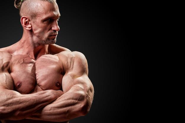 Concetto di sport. atleta di fitness con muscoli perfetti pone