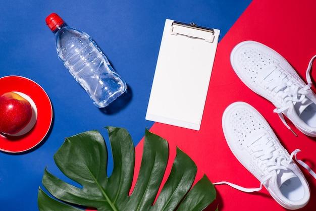 Concetto di sport. attrezzature per il fitness. scarpe da ginnastica, acqua, mela, manubri su sfondo colorato.
