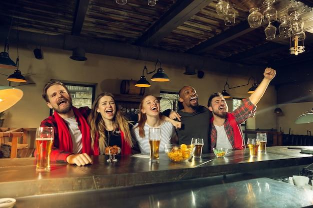 Gli appassionati di sport fanno il tifo al bar, al pub e bevono birra durante il campionato, la competizione sta andando. gruppo multietnico di amici entusiasti di guardare la traduzione. emozioni umane, espressione, concetto di supporto.