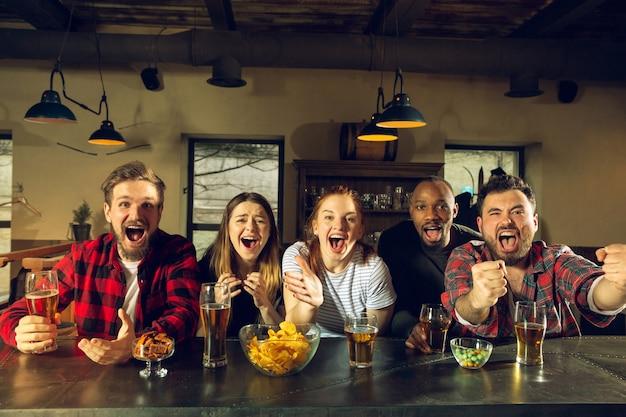 Gli appassionati di sport fanno il tifo al bar pub e bevono birra mentre sta andando la competizione del campionato