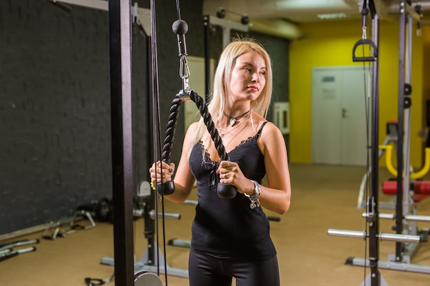 Concetto di sport, fitness, stile di vita e persone - bella donna che flette i muscoli sulla macchina della palestra