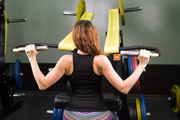 Concetto di sport, fitness, stile di vita e persone - chiuda in su della giovane donna che flette i muscoli sulla macchina della palestra del cavo
