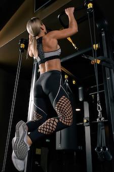 Sport, forma fisica, stile di vita e concetto della gente - donna che si esercita e che fa i pull-up in palestra dalla parte posteriore