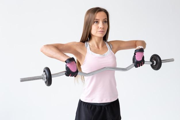 Concetto di sport, fitness e persone - bella giovane donna che fa allenamento con bilanciere.