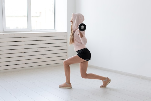 Sport, fitness e concetto di persone - bella giovane donna che si esercita accovacciata con bilanciere.