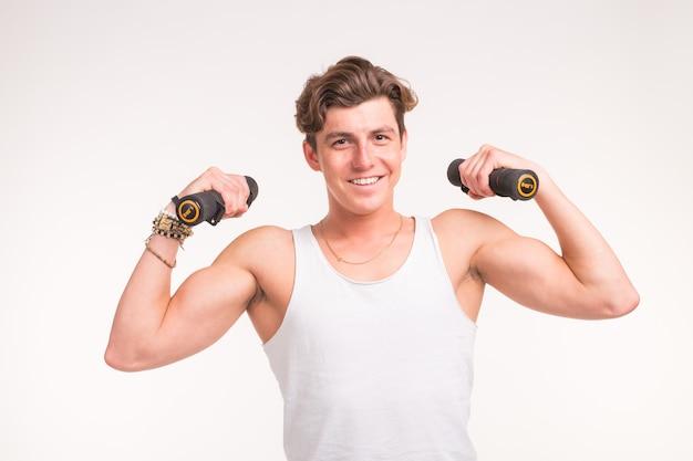 Concetto di sport, fitness e persone - bell'uomo atletico con manubri sul muro bianco.