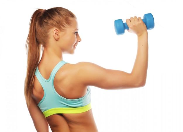 Sport, forma fisica e concetto della gente: donna nella pratica dell'attrezzatura sportiva con i pesi della mano isolati su fondo bianco