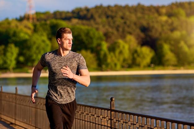 Corridore sportivo e fitness uomo che corre nel parco